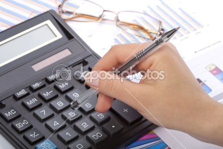 woman's hand holding pen over calculator with paperwork & glassed in background
